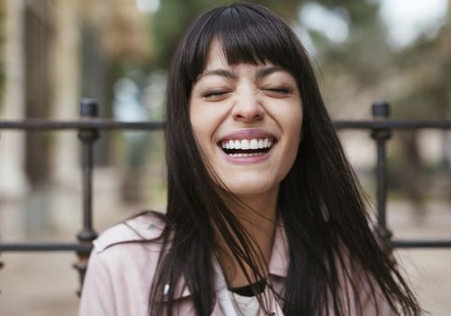 Brunette woman with bangs, laughing