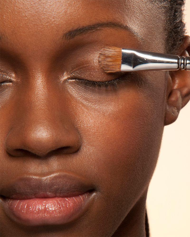 closeup of makeup brush on woman's eyelid