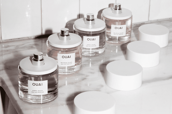 ouai perfumes in a row on marble countertop