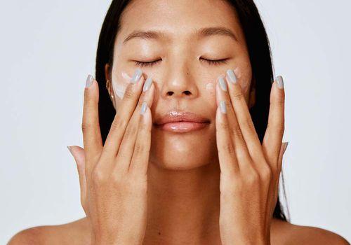 person applying face lotion retinol