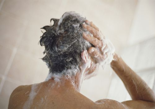 Man taking a shower and washing his hair, rear view.