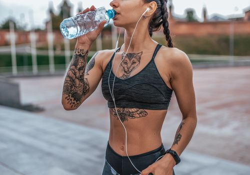 Tattooed woman with braids, in a sports bra and yoga pants, listening to music on a smartphone