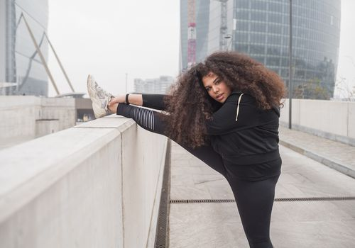 Woman stretching on a bridge in fitness clothes