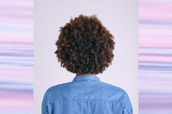 Back View Of African American Woman With Brown Curly Hair.