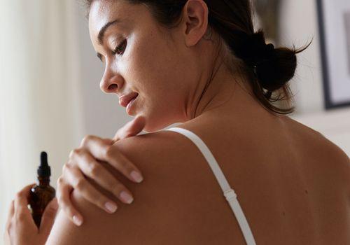 Woman applying oil to dry skin