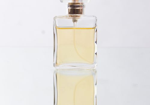 close up of perfume sprayer against white and mirrored background