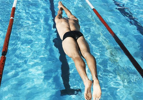 Waxed man in speedo diving into a pool