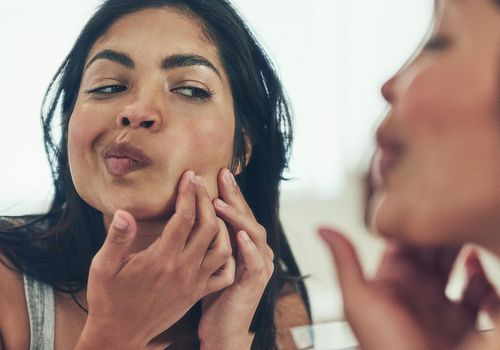 Woman inspects her skin in a mirror.