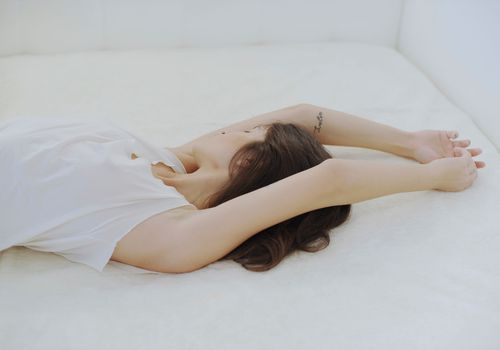 woman laying on bed with her arms over her head