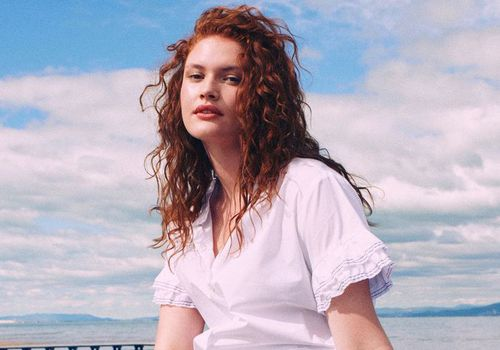 woman with red curly hair at the beach