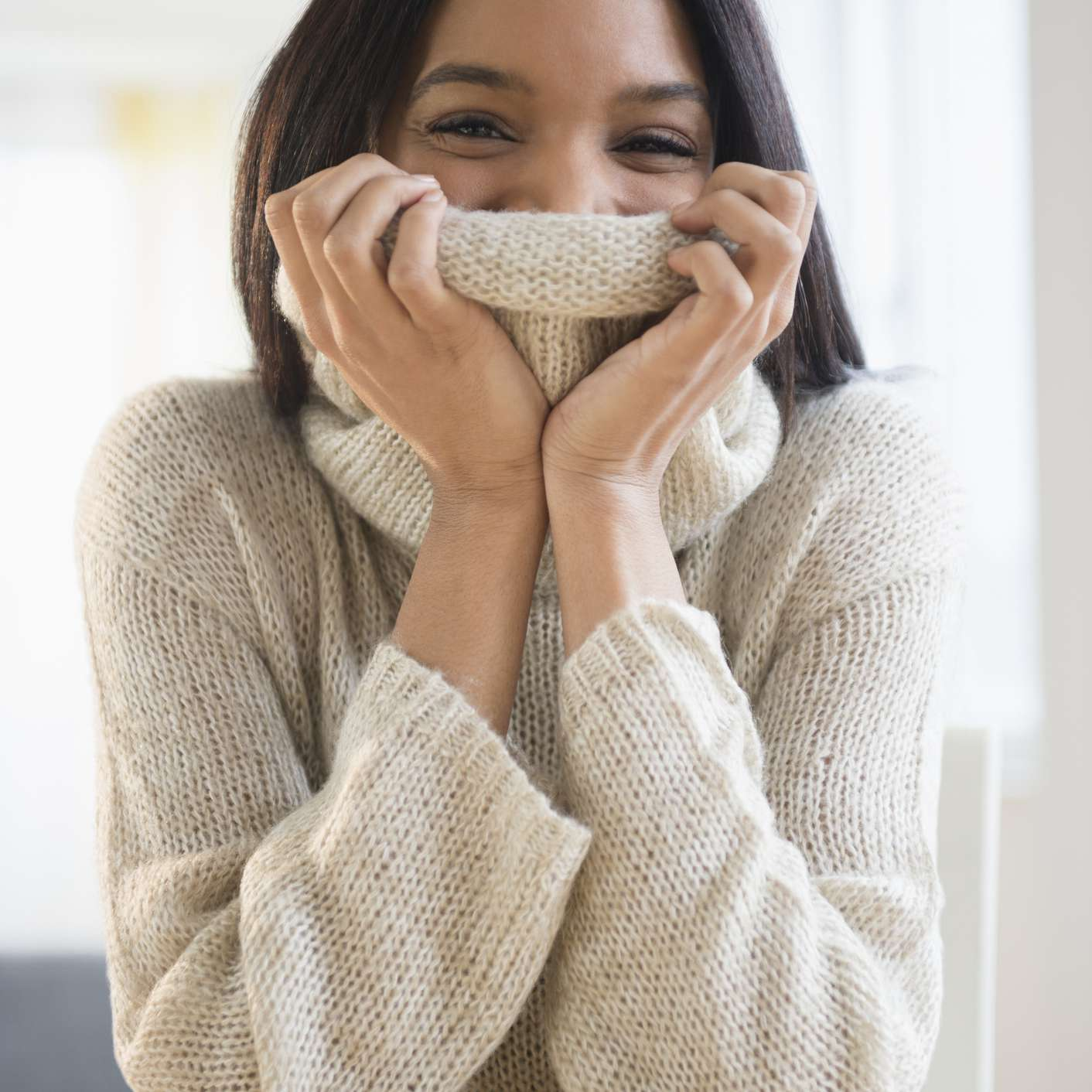 woman covering her chin with sweater
