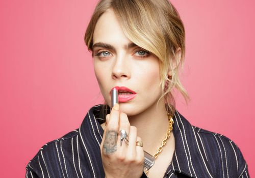 Cara delevingne with her hand showing