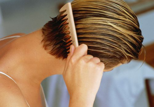 Woman combing short wet hair