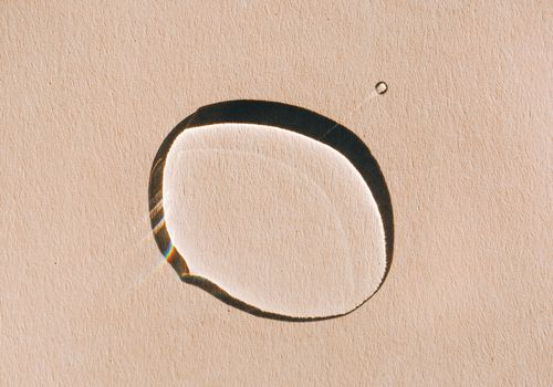 droplet of skincare oil on tan background