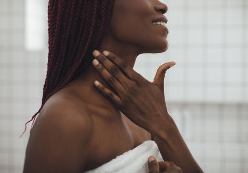 Woman with a deep skin tone applies skincare products to her neck.