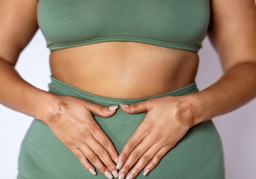 Woman standing with hands over stomach