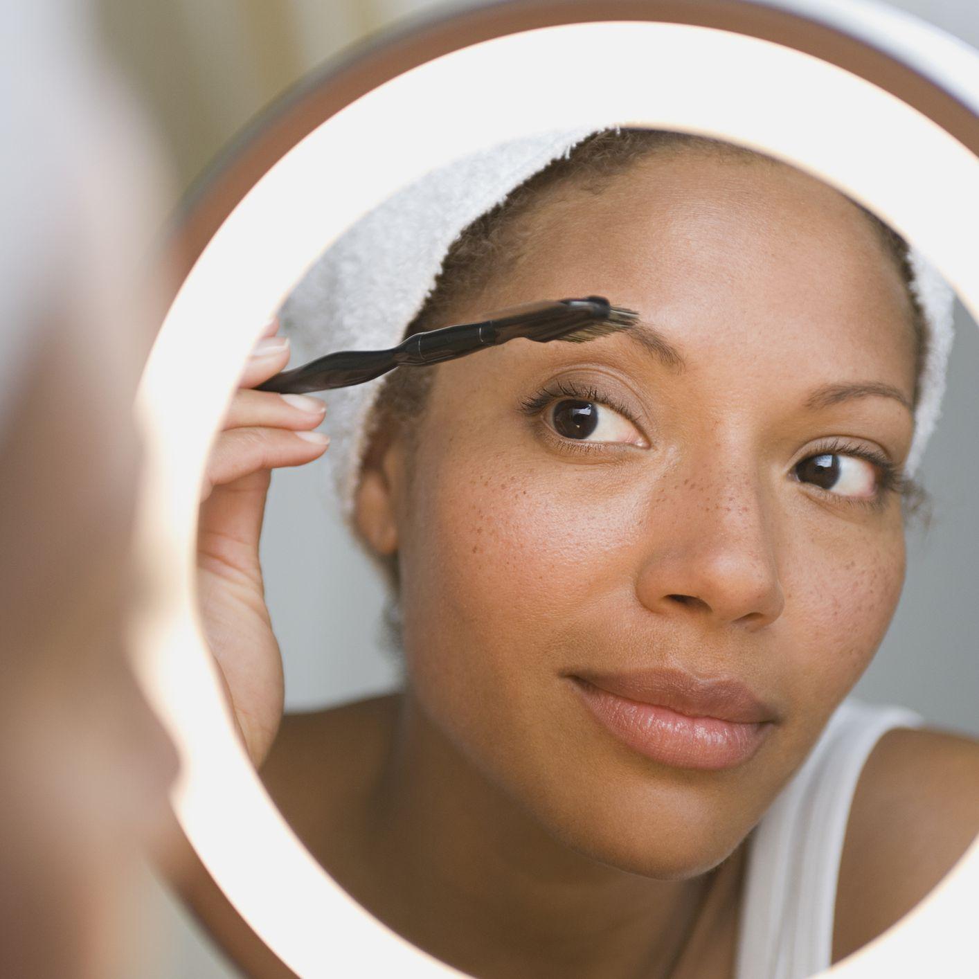 woman grooming brows in beauty mirror