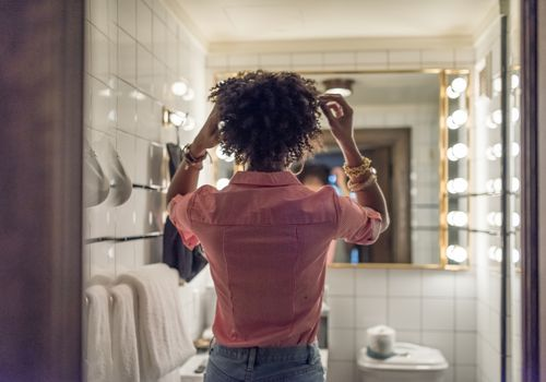 Woman fixing her hair in the bathroom mirror