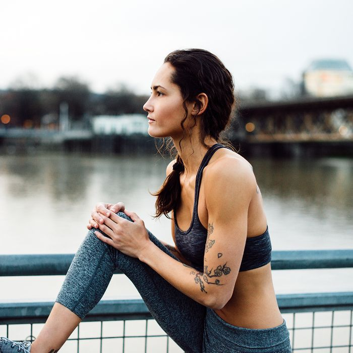 Best Running Jackets: Woman in running gear stretching