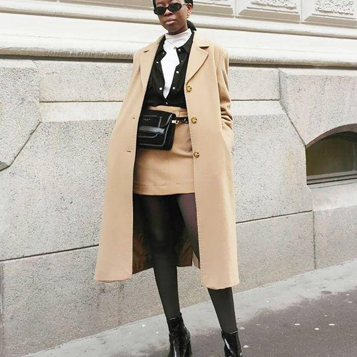 Young woman wears a turtleneck beneath retro-inspired neutrals