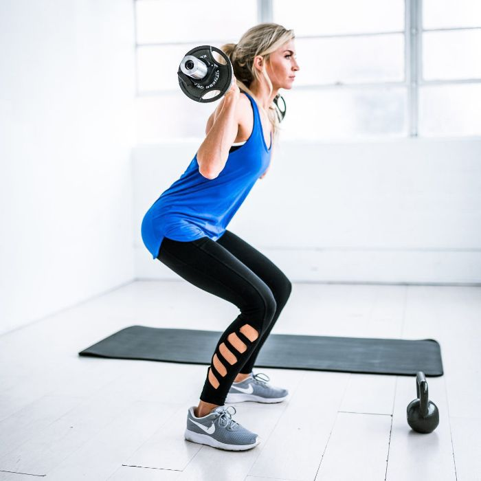 Woman squatting with weighted bar
