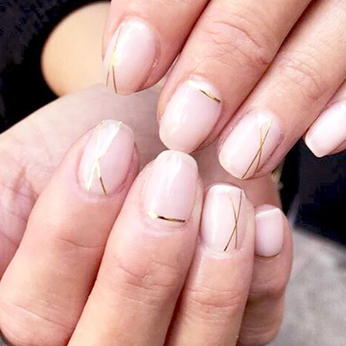 Two hands with minimal gold line manicure