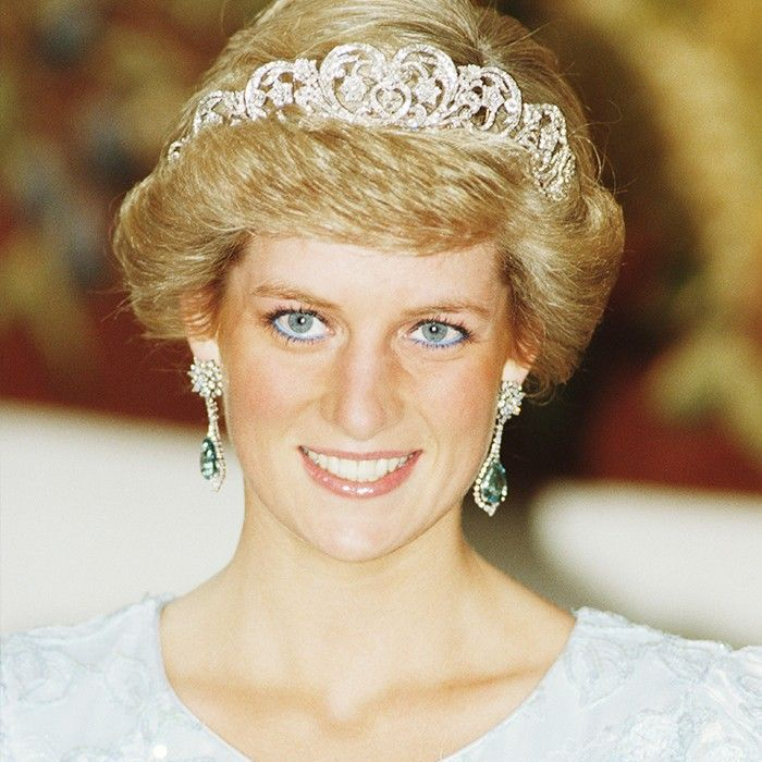 Princess Diana smiling and wearing white dress and tiara