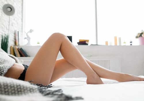 Woman with nice legs laying on bed