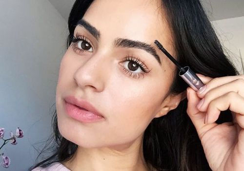 woman with thick eyebrows applying eyebrow gel