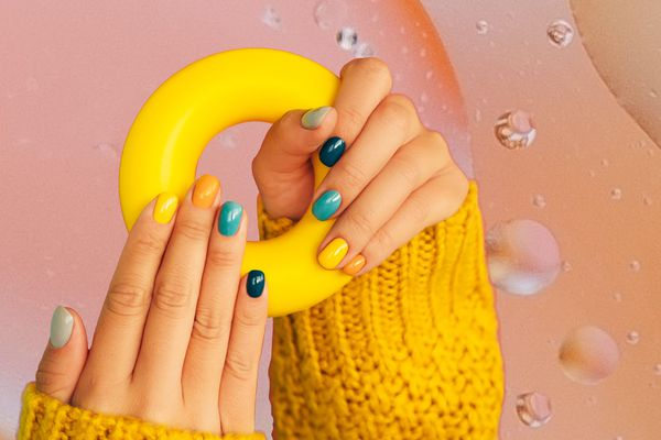 Photo composite of a woman holding a rubber ring, showing off their multi-colored manicure.