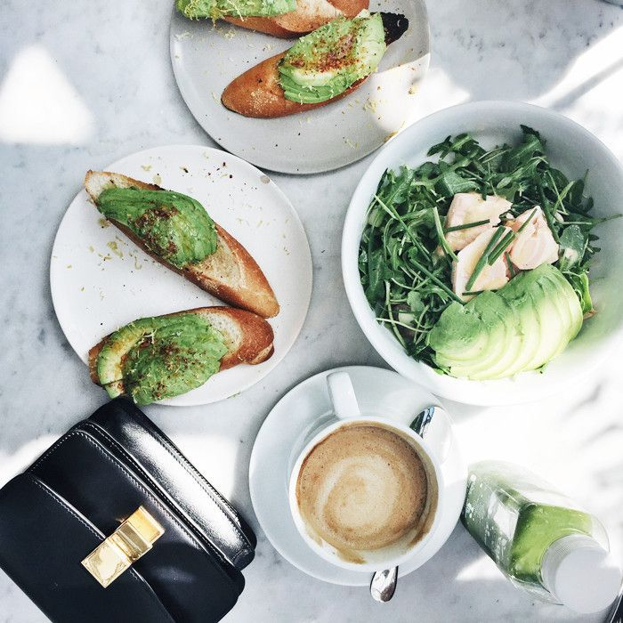 Avocado toast, green salad, latte, green juice, and a black purse