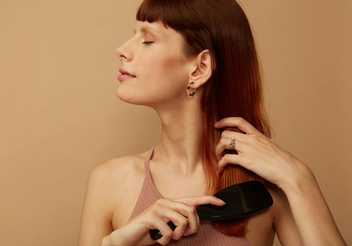 Woman brushes her red hair.