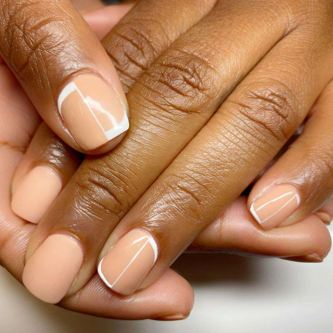 Person with white outlines on nude nails