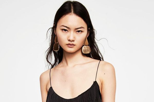 Woman with clear skin wearing gold earrings and black dress