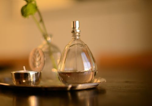 Perfume bottle next to tealight on table