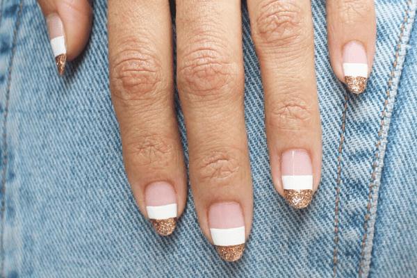 gold and white block stripe nail design against denim background