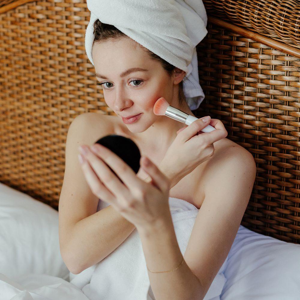 person applies makeup after shower