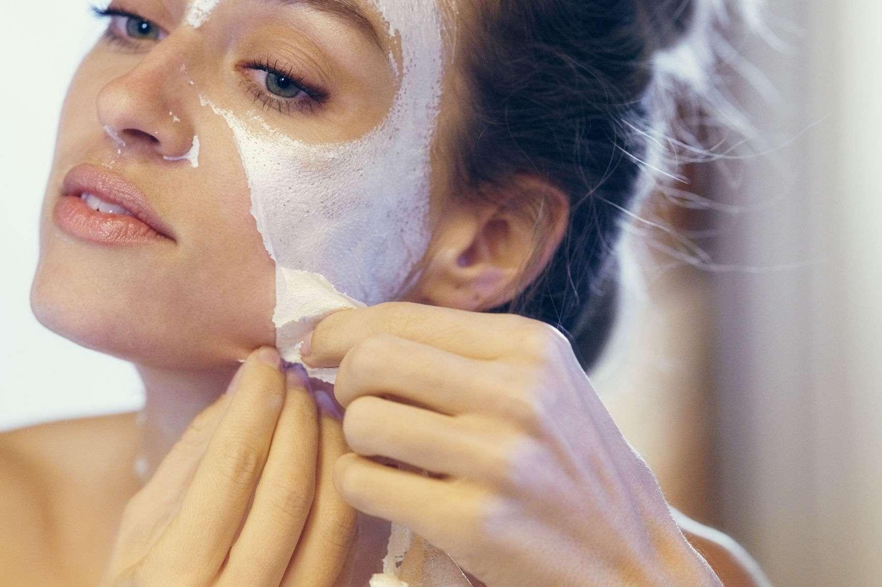 woman peeling off a face mask