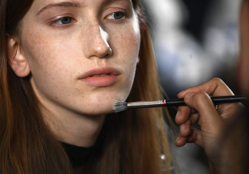 Model having makeup applied backstage at fashion show