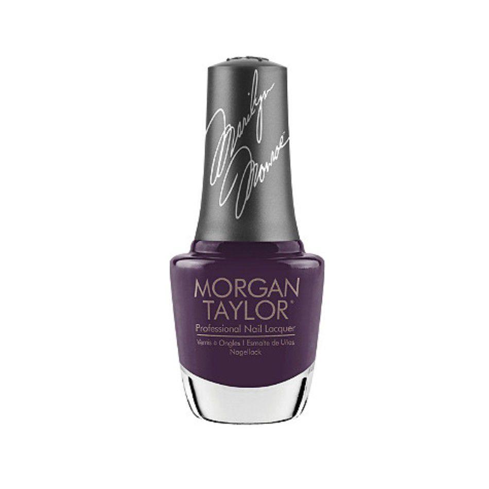 Bottle of dark purple nail polish on a white background.
