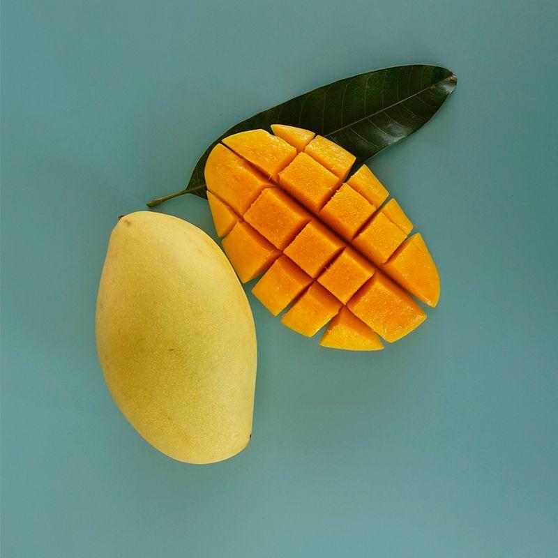 open faced mango on teal backdrop