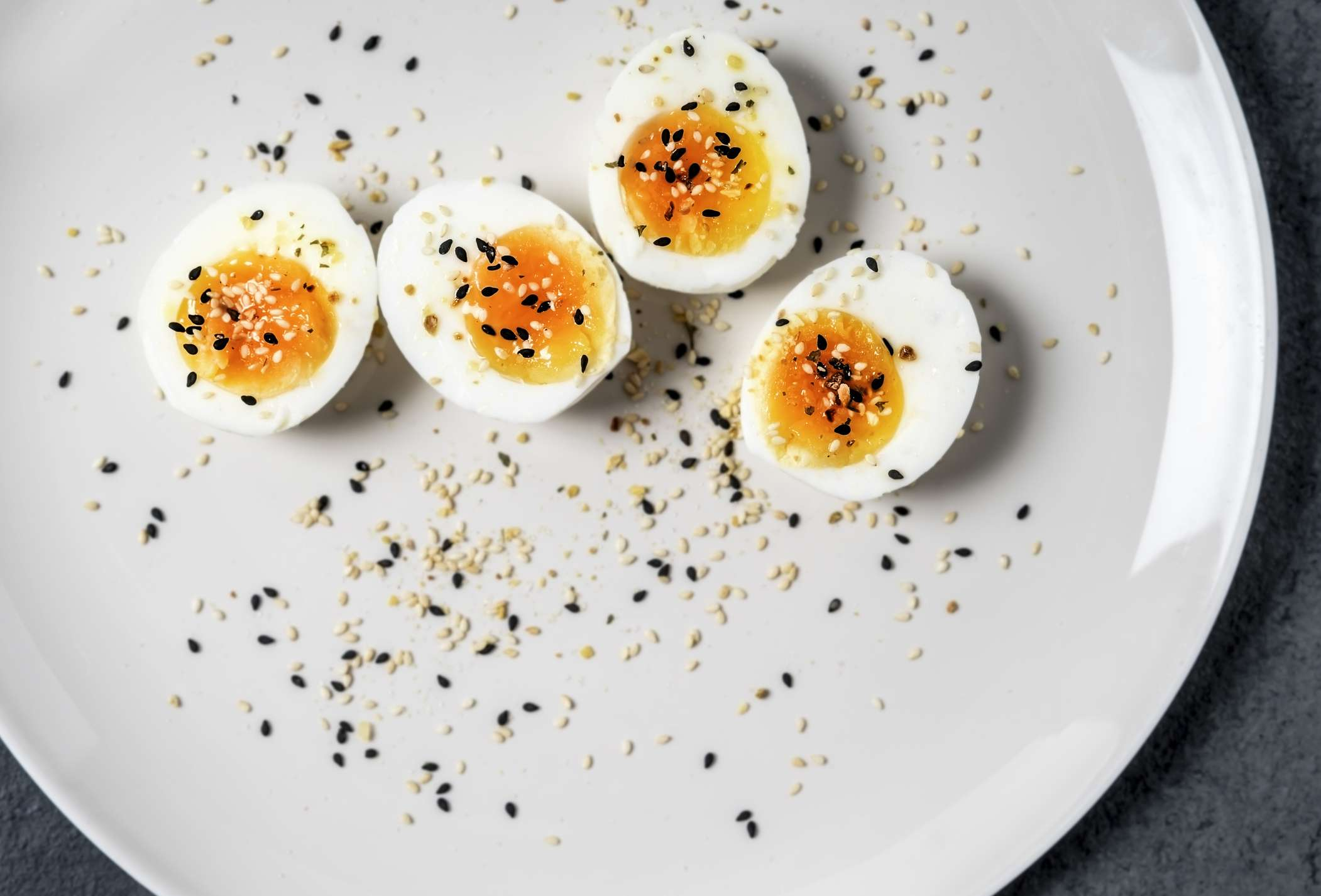 Two halved hard-boiled eggs on a plate, topped with sesame and poppy seeds.