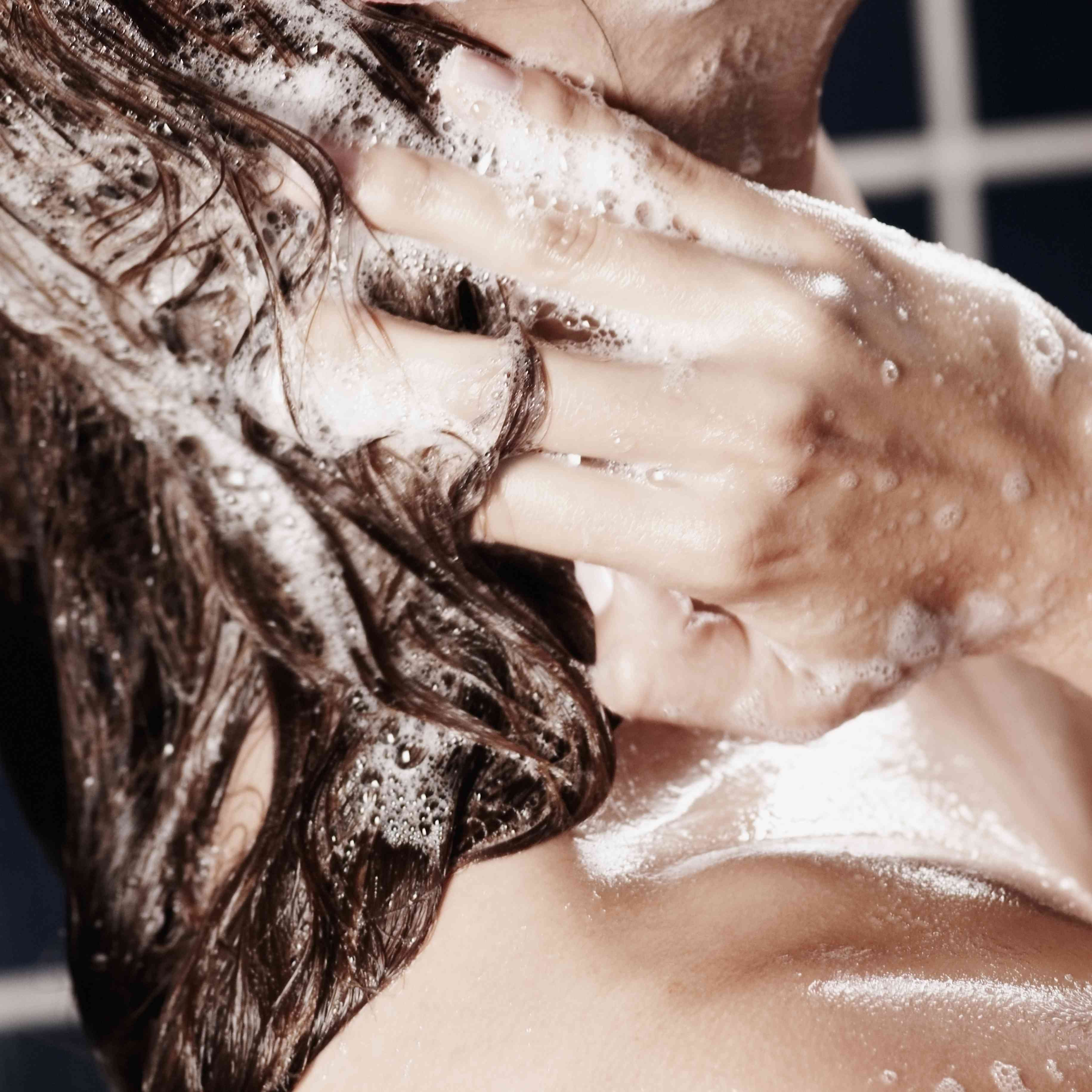 Side profile of a young woman washing her hair with shampoo