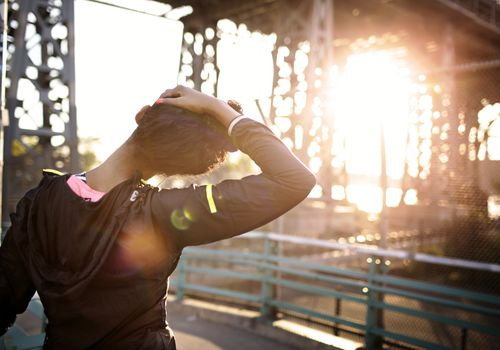 Woman stretching her neck at sunrise.