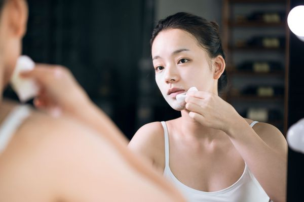 woman putting essence on face