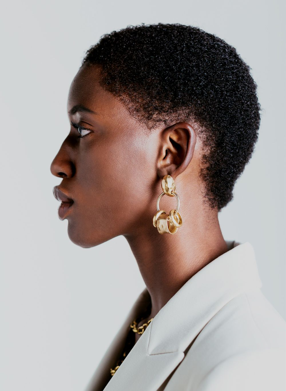 profile of person with chunky gold earrings