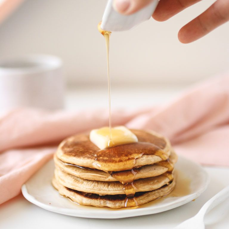 a stack of pancakes with syrup being poured on top