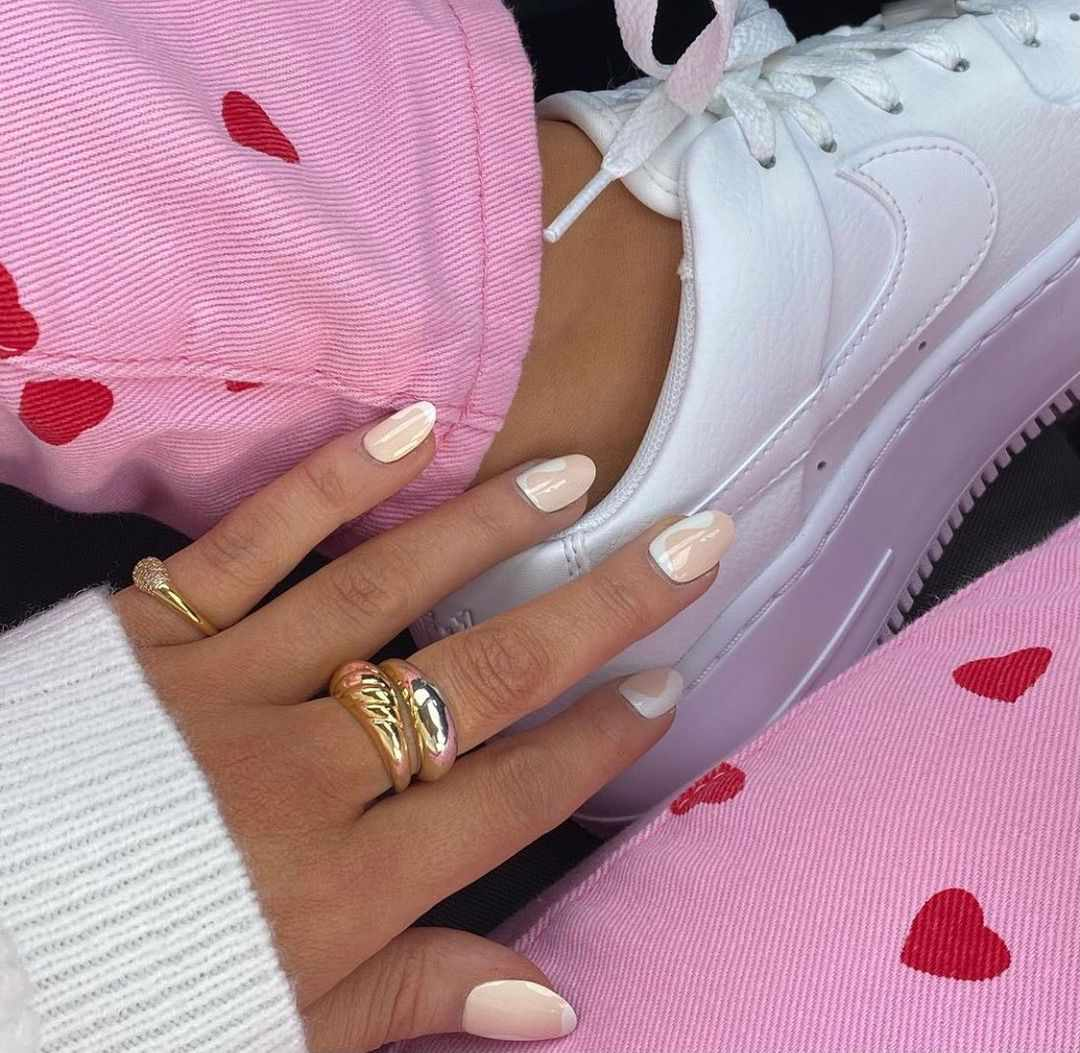 Person with pale nude and white swirl nails.