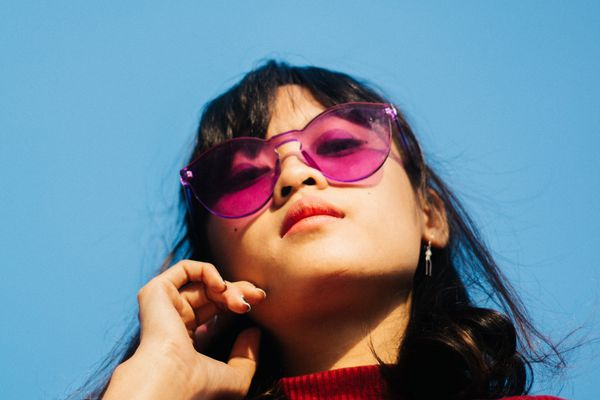 woman in sunglasses outside touching her face