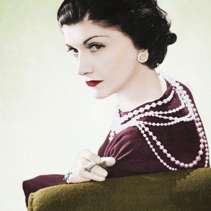 Coco Chanel wearing pearls and smoking a cigarette